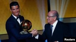 Pemain depan Real Madrid dan Portugal Cristiano Ronaldo menerima piala FIFA Ballon d'Or dari Presiden FIFA Joseph Blatter dalam upacara di Zurich (12/1). (Reuters/Ruben Sprich)