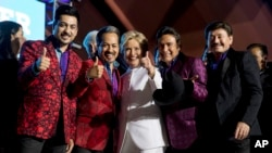 Democratic presidential candidate Hillary Clinton, center, pose with members of the band Los Tigres del Norte at a debate watch party at the Craig Ranch Regional Amphitheater in North Las Vegas, Oct. 19, 2016.