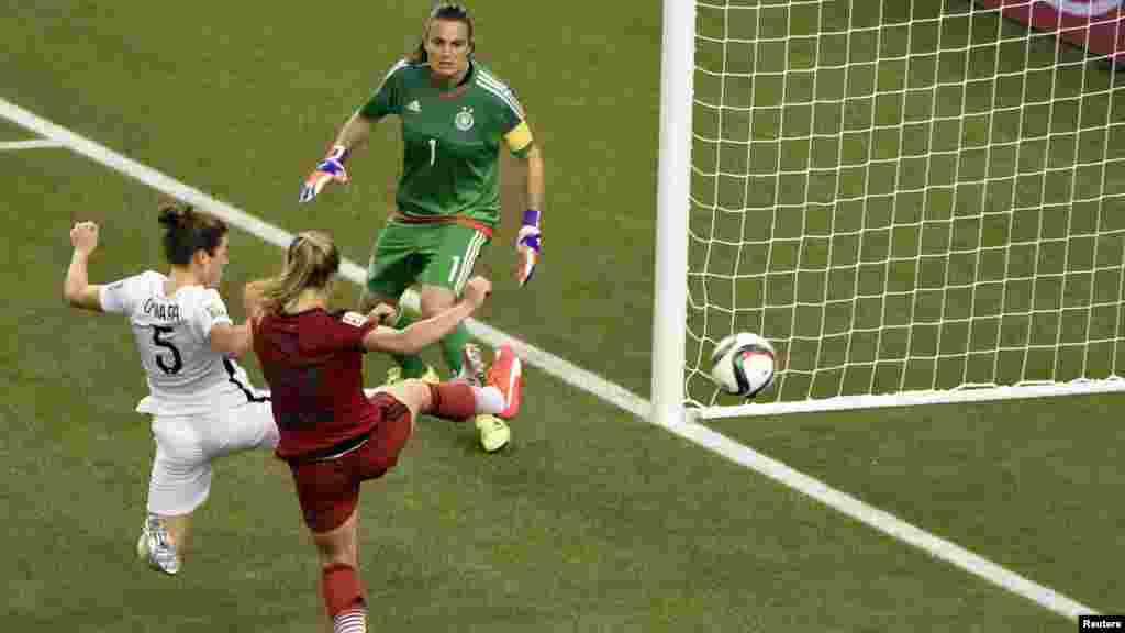 La défenseuse américaine Kelley O'Hara (5) marque contre la gardienne allemande Nadine Angerer (1) au cours de la deuxième moitié de la demi-finale de la Coupe du Monde/Dames 2015 de la FIFA au Stade olympique, le 30 juin 2015 à Montréal, Québec. Credit: