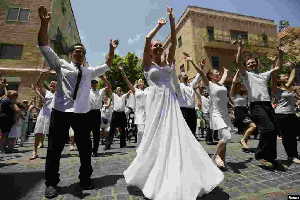 Israelis dressed as brides and grooms dance during a flash mob event promoting gender equality, in Jerusalem.
