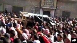 电视截屏显示,12月20号叙利亚人在霍姆斯抬着一名死者的尸体表示抗议