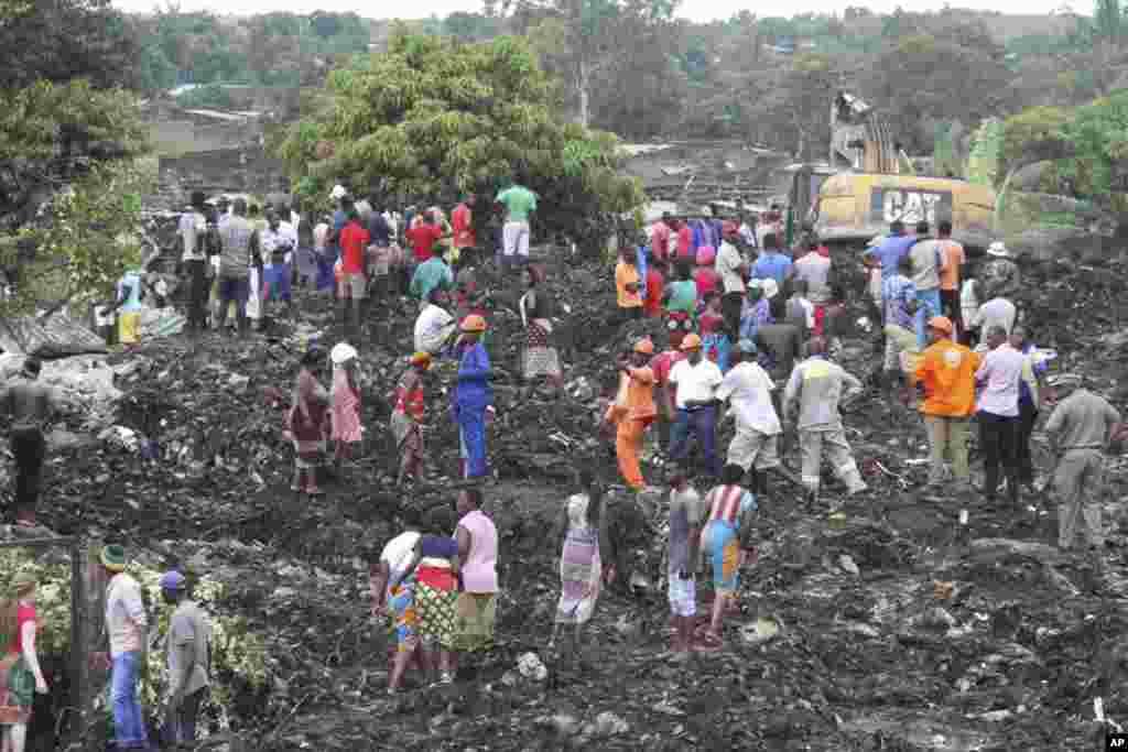 Petugas penyelamat mencari para korban yang tertimbun sampah longsor diMaputo, Mozambik, setelah gunung sampah besar yang longsor menghancurkan beberapa rumah dan menewaskan sedikitnya 17 orang.