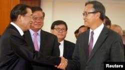 PM Kamboja Hun Sen (kiri) dan pemimpin Partai Penyelamat Nasional Kamboja (CNRP) Sam Rainsy, saling berjabat tangan seusai pertemuan di Phnom Penh (16/9).