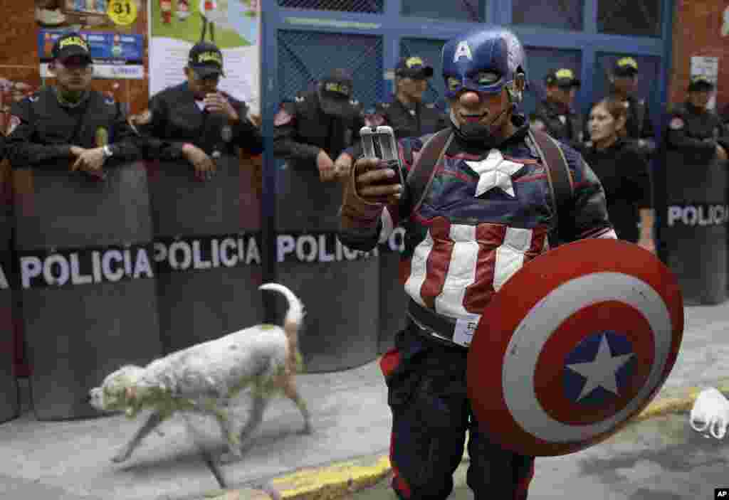 A clown dressed as comic book character Captain America chats with a friend as he takes part in a march celebrating Peruvian Clown Day in Lima, Peru.