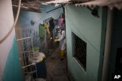 In this Jan. 26, 2016 photo, a municipal worker sprays insecticide to combat the Aedes aegypti mosquitoes that transmits the Zika virus, at the Imbiribeira neighborhood in Recife, Pernambuco state, Brazil.