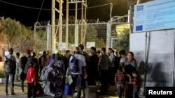Para pengungsi dan migran berkumpul di gerbang kamp Moria, pulau Lesbos, Yunani, menyusul kebakaran di fasilitas tersebut (19/9).