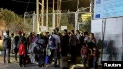 2016年9月19日部分难民和移民在莫里亚难民营发生火灾后聚集在入口处。