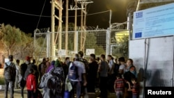 Refugiés et migrants attendent devant une porte fermée au camp de Moria migrant, sur l'île de Lesbos, Grèce,le 19 septembre 2016.