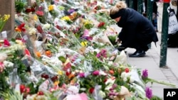 People place flower tributes at the synagogue in Copenhagen, Denmark, Feb. 16, 2015.