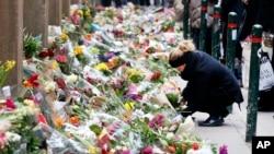16일 덴마크 코펜하겐의 유대교 회당 앞에서 방문객들이 총격 사건 희생자를 애도하는 꽃을 놓고 있다.