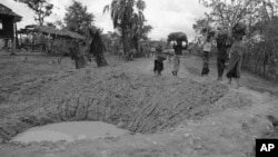 Cambodian villagers walk around bomb crater in a road near embattled Takeo 42 miles southwest of Phnom Penh in Cambodia May 17, 1973. US jets continue to support Khmer government troops against insurgent forces throughout Cambodia despite criticism and threatened congressional action to force an end to the bombing. (AP Photo/Chhor Yuthy)