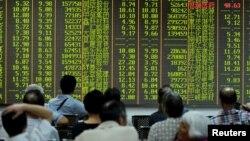 Các nhà đầu tư theo dõi thông tin chứng khoán trên bảng điện tử tại một trung tâm môi giới ở Hàng Châu, tỉnh Chiết Giang.