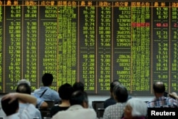 FILE - Investors look at stock information on an electronic board at a brokerage house in Hangzhou, Zhejiang province, Aug. 25, 2015.