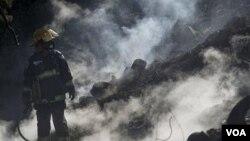 Seorang petugas pemadam kebakaran sedang berusaha memadamkan kebakaran hutan di Israel.