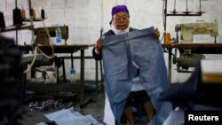Pegawai pabrik garmen di Jakarta sedang mengukur kain untuk celana.
