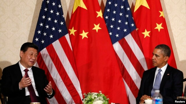 FILE - China's President Xi Jinping speaks during his meeting with U.S. President Barack Obama (R), on the sidelines of a nuclear security summit, in The Hague, March 24 2014.