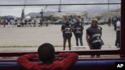 Seorang anak laki-laki mengamati polisi dari atas kapal Ocean Viking di Laut Mediterania, Selasa, 24 September 2019. Dia adalah salah satu di antara 182 orang migran yang diselamatkan di Laut Mediterania, utara Libya. (Foto AP / Renata Brito)