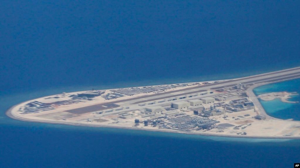 菲律賓空軍一架運輸機在南中國海南沙群島的中國製造的人造島礁渚碧礁上空飛越時拍攝的照片,顯示人造島礁上的簡易機場和建築物。 (2017年4月21日)