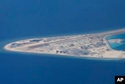 菲律賓空軍一架運輸機在南中國海南沙群島的中國造的人造島礁渚碧礁上空飛越時拍攝的照片,顯示人造島礁上的簡易機場和建築物。(2017年4月21日)