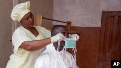 12일 시에라 리온의 한 보건소에서 간호사가 동료에게 에볼라 감염을 막기 위한 마스크를 씌워주고 있다.