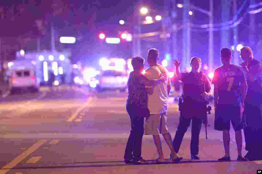Orlando Police officers direct family members away from a multiple shooting at a nightclub in Orlando, Fla., Sunday, June 12, 2016. A gunman opened fire at a nightclub in central Florida, and multiple people have been wounded, police said Sunday.