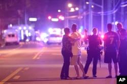 Polisi Orlando mengarahkan keluarga menjauhi lokasi penembakan di sebuah klub malam di Orlando, Florida, 12 Juni 2016.