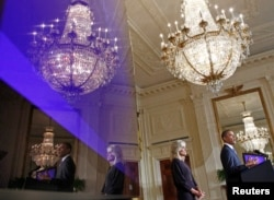 U.S. President Barack Obama and Dr. Jill Biden, wife of U.S. Vice President Joe Biden, are reflected in a monitor at the Community College Summit in the East Room at the White House in Washington, October 5, 2010. REUTERS/Jim Young