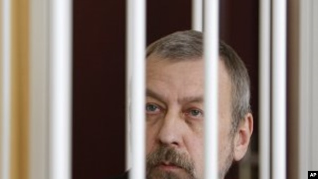 Former presidential candidate Andrei Sannikov sits in a cage during a court hearing in Minsk, April 27, 2011
