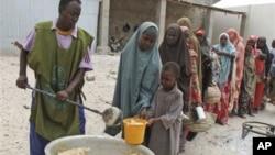 Somalis recebem alimentos num campo em Mogadíscio. Milhares de pessoas chegaram a Mogadíscio nas últimas semanas procurando assistência