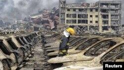 Nhân viên cứu hỏa đi giữa các xe cộ bị thiêu rụi tại hiện trường vụ nổ ở Thiên Tân.