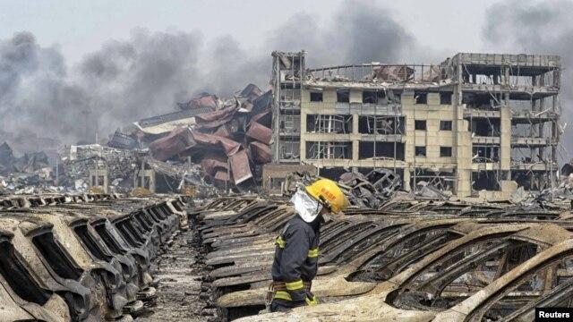 一名消防人员走过天津滨海新区被炸毁的汽车,浓烟从爆炸现场的集装箱中升起。(2015年8月14日)