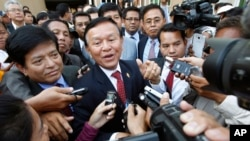 Cambodia's main opposition Cambodia National Rescue Party Deputy President and National Assembly Deputy President Kem Sokha, center, speaks to reporters outside the Phnom Penh Municipality Court in Phnom Penh, Cambodia, Wednesday, April 8, 2015. Sokha appeared at the court on Wednesday to honor his summons to answer questions about the party's protests in 2013 and 2014 against the election results. (AP Photo/Heng Sinith)