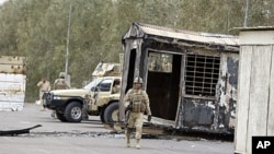 Iraqi Army soldiers stand guard near burned trailers at Camp Ashraf north of Baghdad, Iraq, April 8, 2011 (file photo).