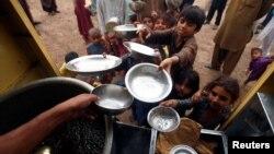 پشاور کے ایک خیراتی مرکز میں بچے اپنے پیالوں لیے خوراک ملنے کا انتظار کر رہے ہیں۔ 13 مارچ 2018