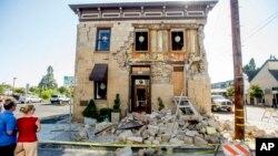 FILE - Pedestrians stop to examine a crumbling building facade in Napa, California, following an earthquake, Aug. 24, 2014.