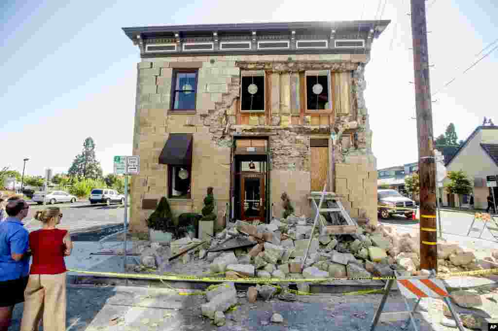 Pedestrians stop to examine a crumbling facade at the Vintner's Collective tasting room in Napa, California, following an earthquake, Aug. 24, 2014.
