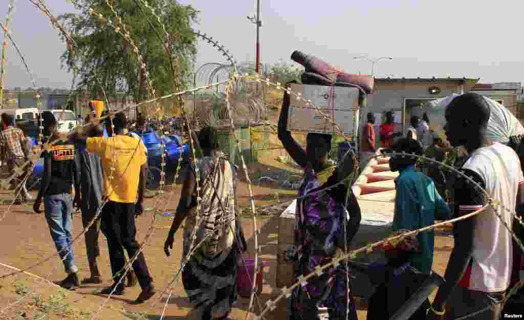 Displaced people walk past razor wire at Tomping camp, near Juba, South Sudan, Jan. 7, 2014.