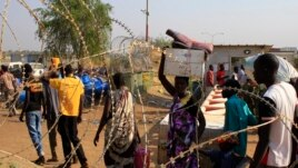 Displaced people walk past razor wire at Tomping camp, where some 15,000 displaced people who fled their homes are sheltered by the United Nations, near Juba, South Sudan, Jan. 7, 2014.