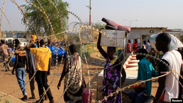 Displaced people walk past razor wire at Tomping camp, where some 15,000 displaced people are sheltered by the United Nations, near Juba, South Sudan, Jan. 7, 2014.