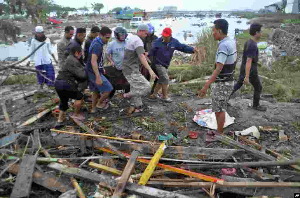Residents carry a body bag containing the body of a tsunami victim in Palu, Central Sulawesi, Indonesia, Sept. 29, 2018.