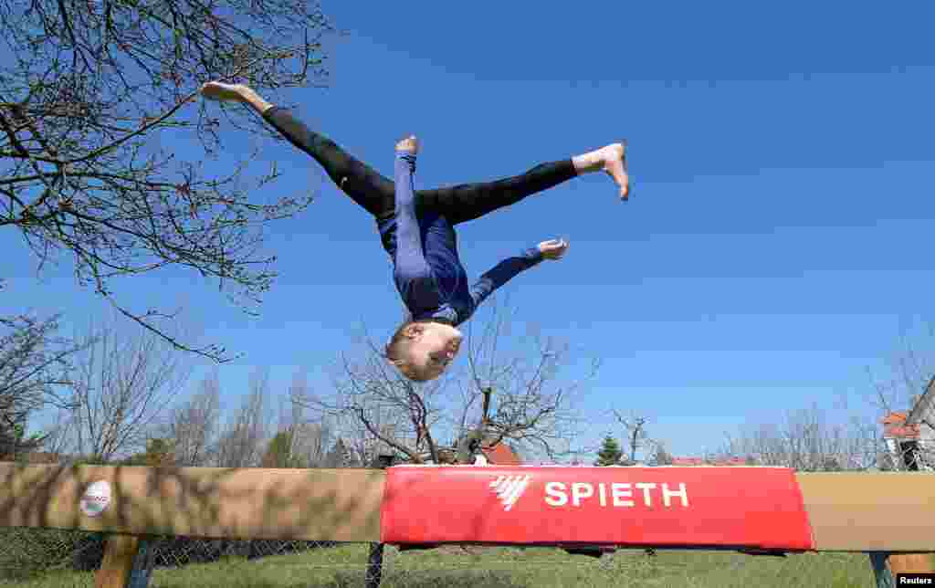 Clara Neumann, gymnast of the sports club Dresdner SC, trains in her parent's garden in Dresden, Germany, April 1, 2020.
