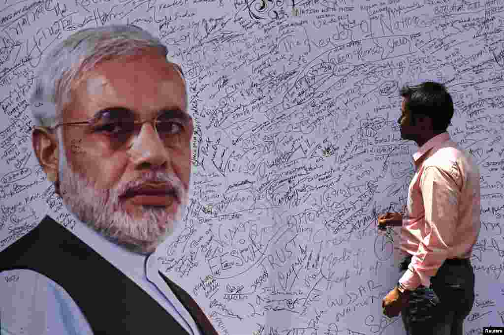 A man prepares to sign a board with a picture of Hindu nationalist Narendra Modi, the presumptive prime minister of India and leader of the opposition Bharatiya Janata Party (BJP), at the BJP headquarters, in New Delhi, May 16, 2014.