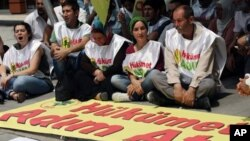 Kurds sit next to a banner that reads 'government, take steps' after Kurdish rebels gave Turkey a 'final warning' to take steps that would move forward peace talks aimed at ending a 30-year old conflict that has claimed tens of thousands of lives, in Anka