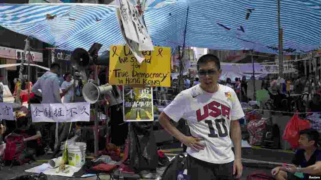 """O elemento do movimento """"Ocupar o Centro"""" de guarda na estrada principal do distrito de Mong Kok em Hong Kong, Out. 6, 2014."""