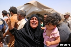 FILE - A women who fled Ramadi holds a child in a camp in the town of Amiriyat al-Fallujah, west of Baghdad, Iraq, May 22, 2015.