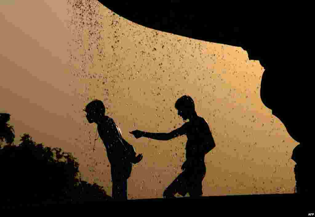 May 3: Indian children cool themselves at a water fountain on a hot afternoon in New Delhi. (AP Photo/Tsering Topgyal)
