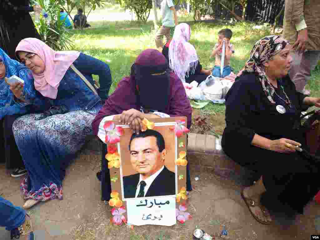 "A woman sits outside the hospital where Mubark is being treated. She holds a sign saying ""Mubarak is innocent,"" Cairo, Oct. 6, 2015. (H. El Rasam/VOA)"