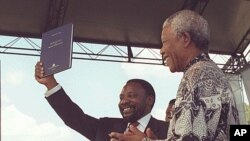Chairman of the Constitutional Assembly, Cyril Ramaphosa, left, holds up a copy of the country's new constitution, was signed by President Nelson Mandela, right, in Sharpville, December 10, 1996. (file photo)