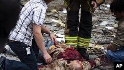 노르웨이 수도 오슬로 정부청사 폭탄테러 현장에서 구조대원들이 희생자를 살펴보고 있다.
