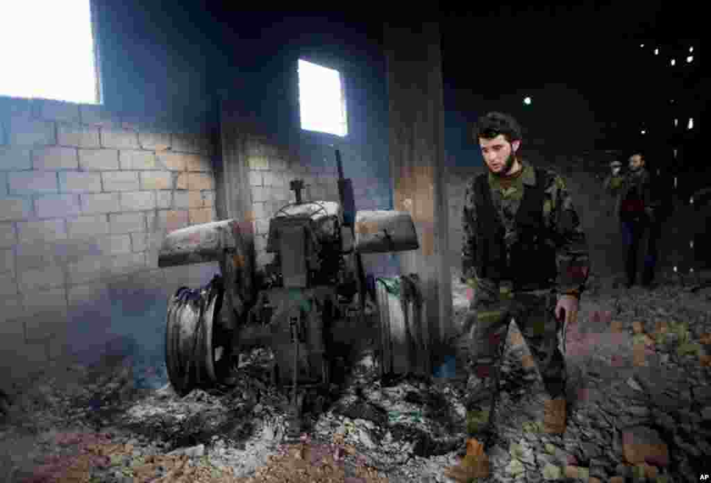 A Free Syrian Army soldier next to a burned tractor in Sarmin, north Syria, February 28, 2012 (AP)